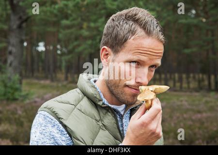 Mid adult man smelling mushroom - Stock Photo