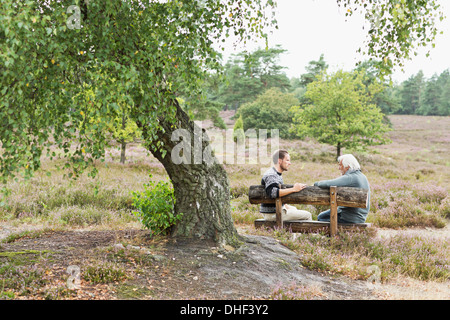 Senior man and mid adult man sitting on bench - Stock Photo