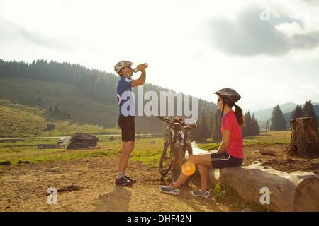 Man and woman resting with mountain bikes, Styria, Austria - Stock Photo