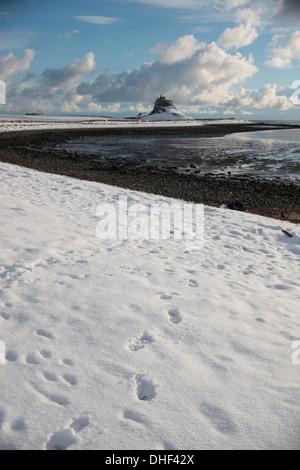 Lindisfarne Castle  a 16th-century castle, Snow on beach at Holy Island - Stock Photo