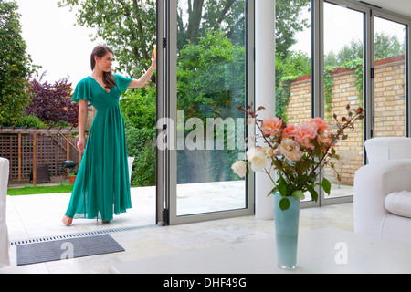 Young woman standing in patio dorrway - Stock Photo