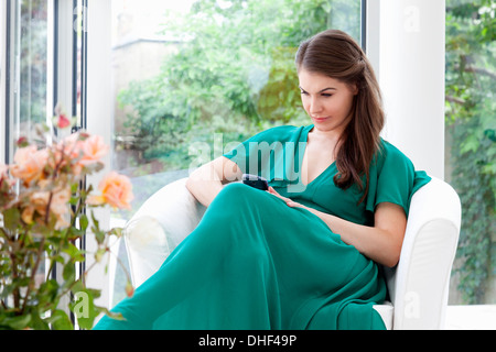 Young woman wearing green dress sitting in armchair - Stock Photo