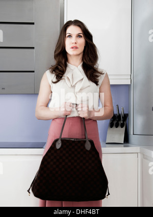 Portrait of young woman holding handbag with blank expression - Stock Photo