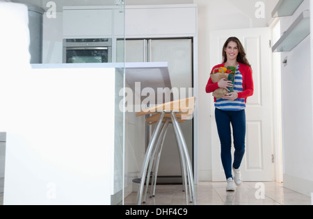 Young woman carrying grocery bag - Stock Photo