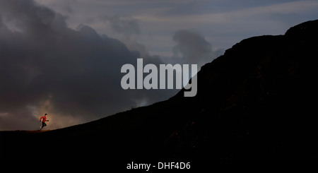 Young man running up silhouetted mountain - Stock Photo