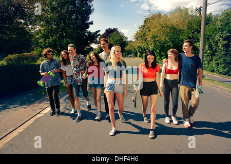 Large group of young adult walking down road - Stock Photo