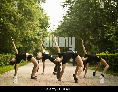 Four young ballet dancers exercising in park - Stock Photo