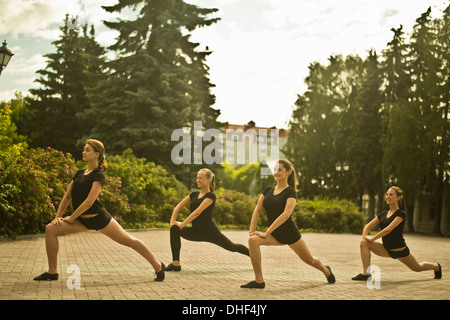 Four young ballet dancers exercising in park gardens - Stock Photo