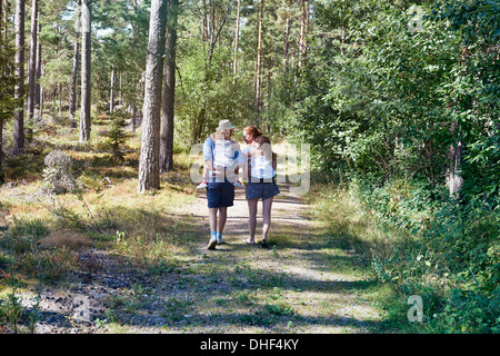 Parents giving daughters piggy back through forest - Stock Photo