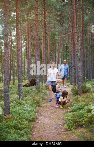 Parents walking through forest with daughters - Stock Photo