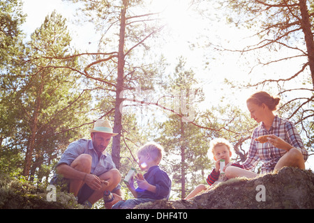 Family having picnic sitting on rocks - Stock Photo