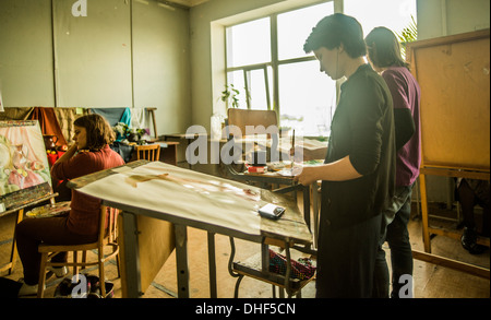 Three young female artists painting in studio - Stock Photo