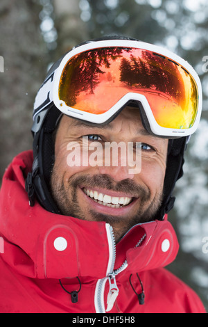 Mid adult man with ski goggles, smiling - Stock Photo