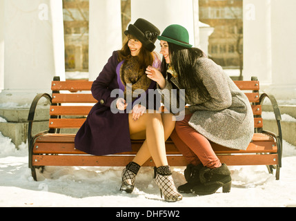 Two young women sitting on park bench in snow - Stock Photo
