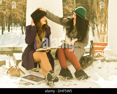 Two young women with books on park bench in snow - Stock Photo