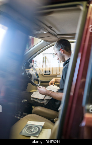 Mechanic sitting in driver's seat of car with manual - Stock Photo