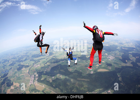 Three skydivers free falling above Leutkirch, Bavaria, Germany - Stock Photo