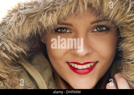 Close up portrait of young woman in parka hood - Stock Photo