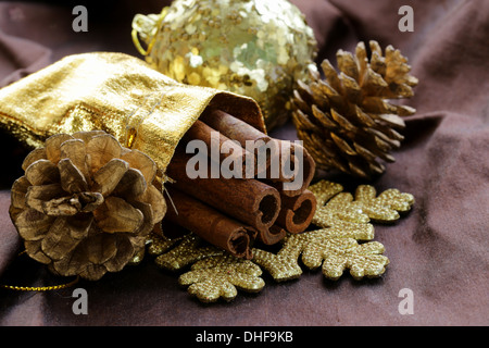 fragrant cinnamon sticks in gold Christmas decorations - Stock Photo