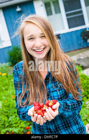 Portrait of smiling young girl with long blond hair holding freshly picked strawberries in her hands - Stock Photo