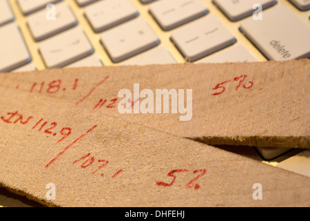 LUMBER HUMIDITY MOISTURE REDUCTION CALCULATIONS OF KILN TIMBER SLICES LAYING ON COMPUTER KEYBOARD - Stock Photo