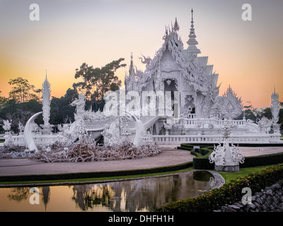 The stunning Wat Rong Khun, popularly known as the White Temple, at sunset in Chiang Rai, Northern Thailand. - Stock Photo