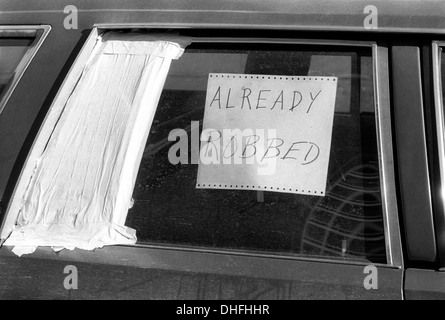 New York, NY - 4 Feb 1987 - Car with broken window and sign that reads 'already robbed.' - Stock Photo