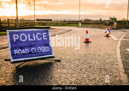 Police road closed sign and traffic cones seal off a road following an incident - Stock Photo