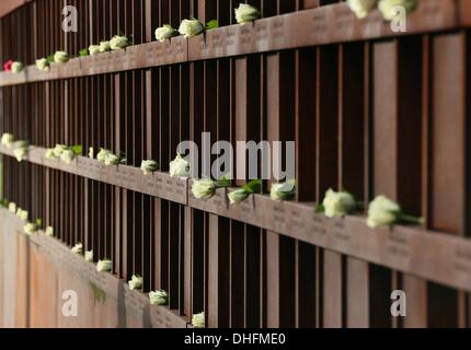 Berlin, Germany. 09th Nov, 2013. White roses are put down at the memorial of the Wall in reminiscence of the fall - Stock Photo