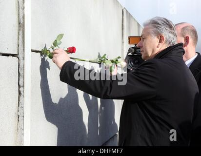 Berlin, Germany. 09th Nov, 2013. Berlin's mayor Klaus Wowereit sticks a rose in a gap of the memorial of the Berlin - Stock Photo