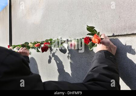 Berlin, Germany. 09th Nov, 2013. Roses stuck in a gap of the memorial of the Berlin Wall in Berlin, Germany, 09 - Stock Photo