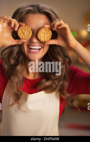 Happy young housewife holding christmas cookie in front of eyes - Stock Photo