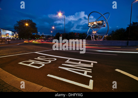 Bus Lane at dusk on a busy roundabout - Stock Photo
