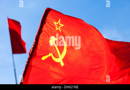 Red flag waving over blue sky background - Stock Photo