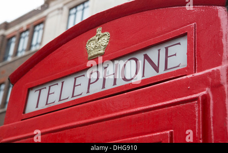 An angled view of a red telephone booth sign in London, England - Stock Photo