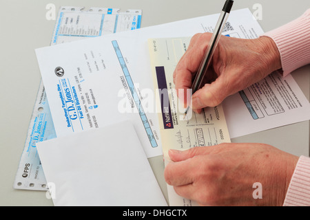 Senior woman pensioner writing a Nat West bank cheque to pay for a large oil fuel bill for home heating in Wales, - Stock Photo