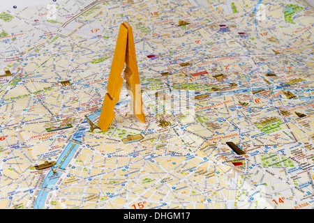 Wooden clamp as Eiffel tower on a map. Conceptual photography - Stock Photo