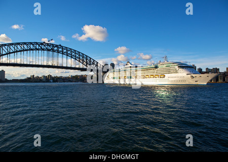 Radiance of the Seas departs Sydney at Dusk, the shadow of the Sydney Harbour Bridge falling on her starboard side. - Stock Photo