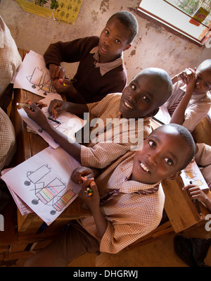 Schoolboys in a Kenyan classroom show off their art works - Stock Photo