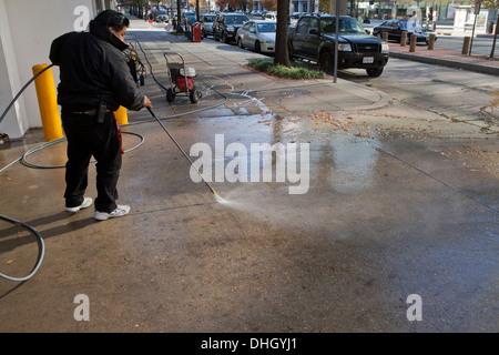 Man power washing walkway - Stock Photo
