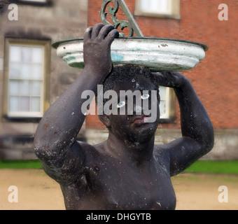 Black African holding sundial at Dunham Massey Hall , near Altrincham Cheshire England , UK WA14 4SJ - Stock Photo