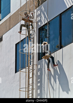 Window cleaners working on a high rise building. Thailand S. E. Asia - Stock Photo