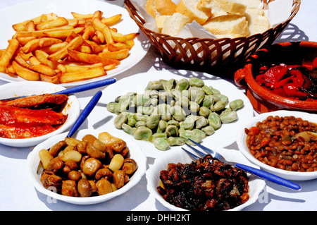 Spanish tapas selection of Sardines, broad beans, mushrooms, onions, peppers, chips, with bread, Andalusia, Spain. - Stock Photo