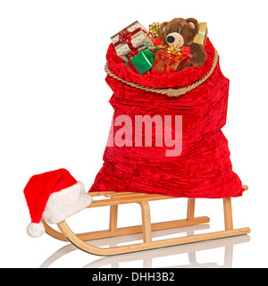 Santa's sack full of gift wrapped Christmas presents and toys on a wooden sledge, isolated on a white background. - Stock Photo