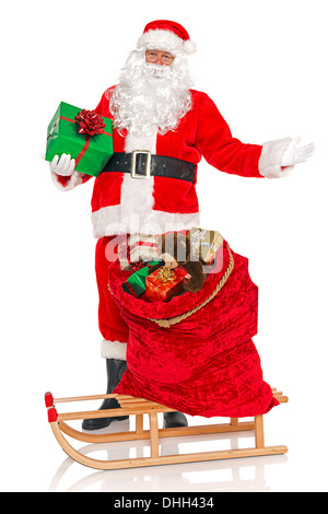 Santa Claus with a sack full of gift wrapped toys and presents on a sledge, isolated on a white background. - Stock Photo