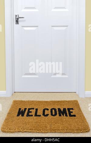 A Welcome doormat in front of a door. - Stock Photo