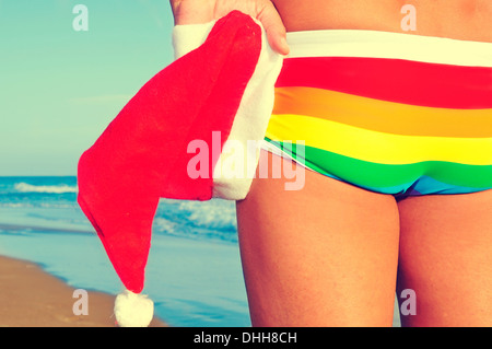 someone at the beach wearing a rainbow swimsuit and holding a Santa hat in his hand - Stock Photo