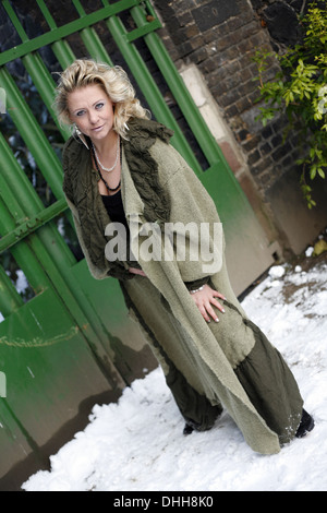 blond woman in a green coat - Stock Photo