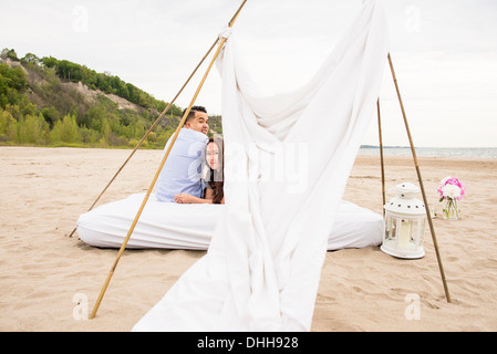 Young couple under canopy on beach - Stock Photo