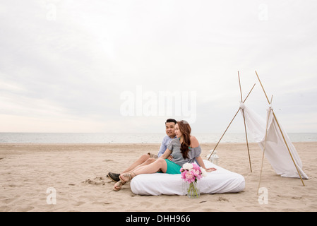 Young couple sitting on mattress canopy on beach - Stock Photo